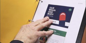 hand pointing to paper in a binder