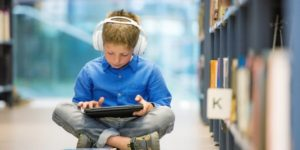 child with headphones reading a tablet