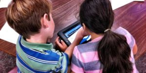 boy and girl looking at a tablet together