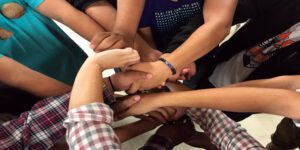 people holding hands in a group circle