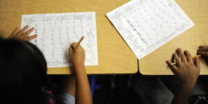 kids filling out paper assignment at table