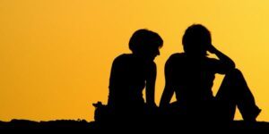 graphic silhouette of two students peers
