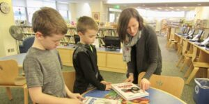 librarian with young students looking at books