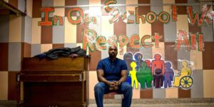 teacher in front of art display that says respect all