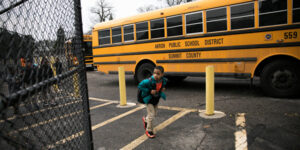young student kid wearing a backpack in front of a school bus