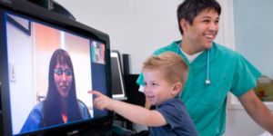doctor with child pointing at monitor screen that displays a therapist