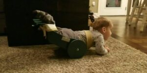 toddler crawling with device supporting back legs