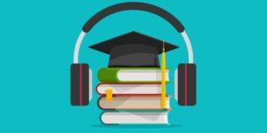 headphones around a graduation cap and books